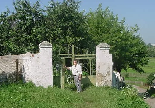 The head of the Jewish community stands at the entrance New Jewish cemetery in Shepetovka, 2001
